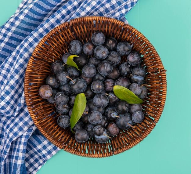 Vue de dessus d'un petit fruit avec une peau foncée prunelles sur un seau sur une nappe à carreaux bleu sur fond bleu