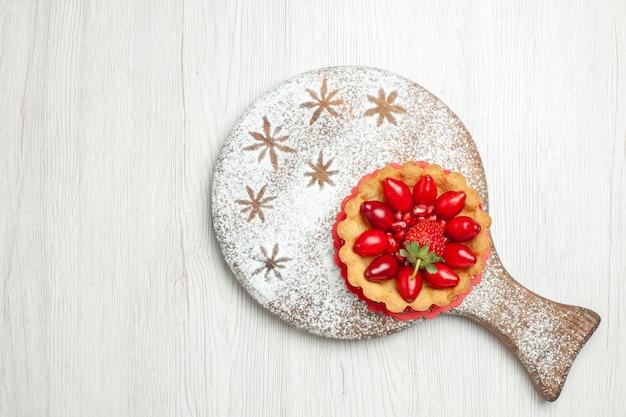 Vue de dessus petit gâteau aux fruits frais sur un bureau blanc
