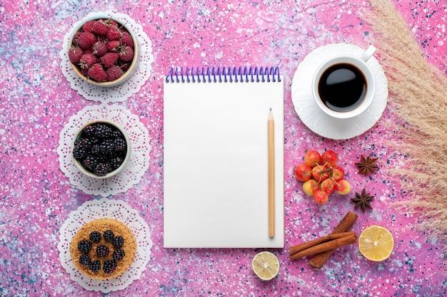Vue de dessus petit gâteau aux mûres avec des framboises fraîches et des mûres tasse de thé sur un bureau rose clair.
