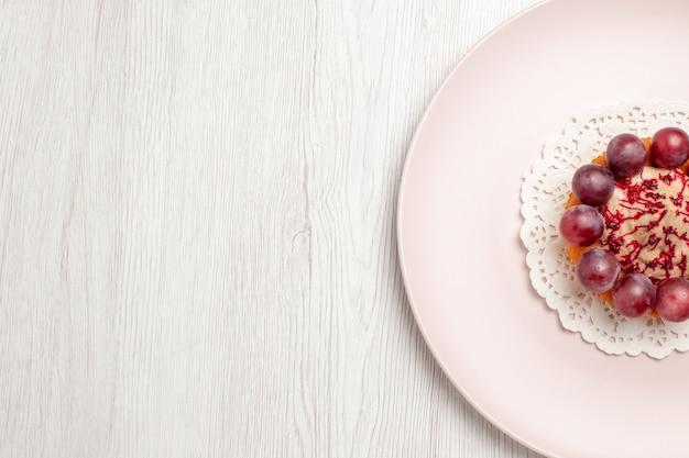 Vue de dessus petit gâteau aux raisins à l'intérieur de la plaque sur le sol blanc gâteau dessert aux fruits