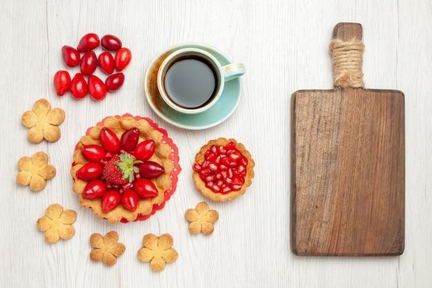 Vue de dessus petit gâteau avec des biscuits aux fruits et une tasse de thé sur un bureau blanc