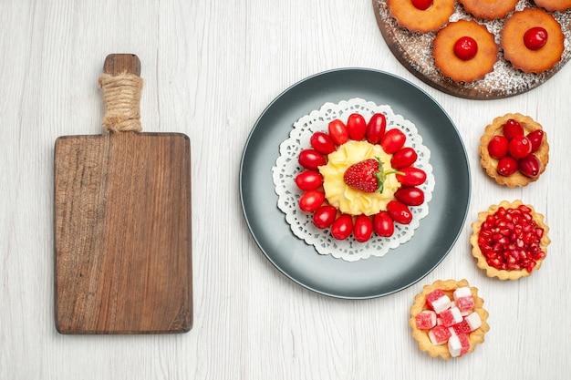 Vue de dessus petit gâteau crémeux avec des gâteaux et des fruits sur un bureau blanc