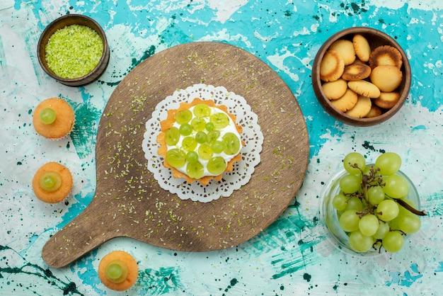 Vue de dessus petit gâteau délicieux avec de la crème délicieuse et des biscuits aux raisins frais et en tranches sur le gâteau de bureau bleu clair couleur de fruits sucrés