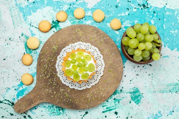 Vue de dessus petit gâteau délicieux avec de la crème délicieuse et des biscuits aux raisins frais et tranchés sur le gâteau de bureau lumière bleue
