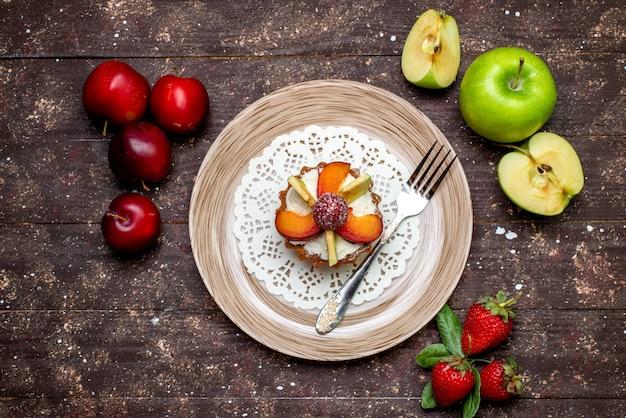 Une vue de dessus petit gâteau délicieux avec de la crème à l'intérieur de la plaque avec des fraises fraîches et des pommes sur le gâteau biscuit cookie fond sombre