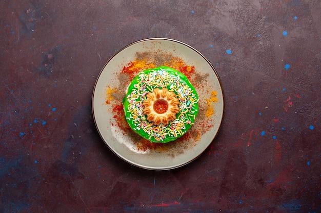 Vue de dessus petit gâteau délicieux avec de la crème verte sur la surface sombre