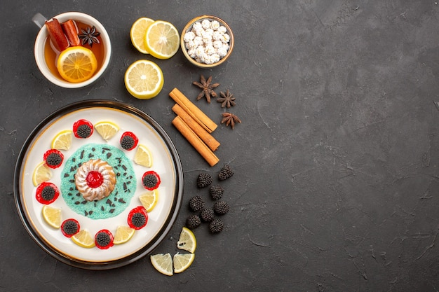Vue de dessus petit gâteau délicieux avec des tranches de citron et une tasse de thé sur fond sombre biscuit aux agrumes aux fruits sucré