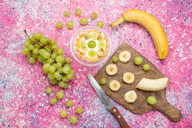 Vue de dessus petit gâteau avec des raisins frais et des bananes sur la surface lumineuse du gâteau aux fruits de couleur douce et fraîche