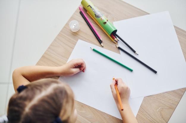 Vue de dessus de la petite fille avec des crayons et une feuille de papier vide sur la table.