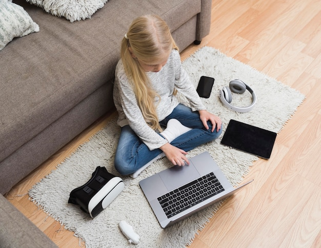 Vue de dessus de la petite fille avec des gadgets sur le sol