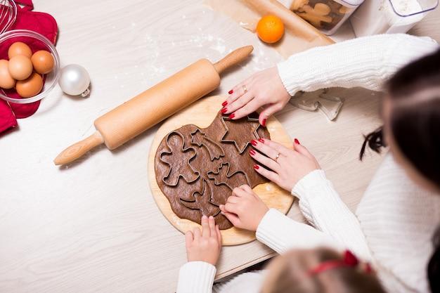 Vue de dessus de la petite fille et de sa mère préparant des biscuits de noël ou des pains d'épice dans la cuisine