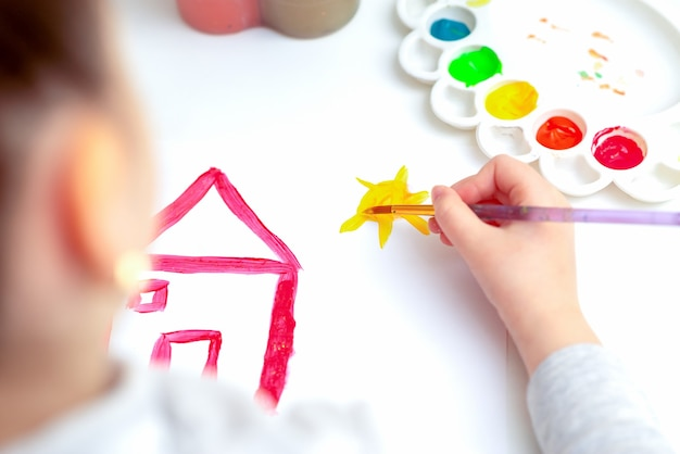Vue de dessus de la petite main de l'enfant dessinant la maison et le soleil à l'aquarelle. concept d'éducation et d'école.