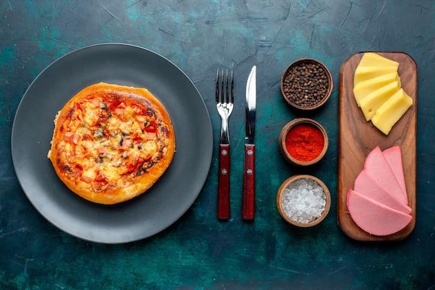 Vue de dessus de la petite pizza au fromage ronde formée avec des assaisonnements de fromage sur la surface bleu foncé