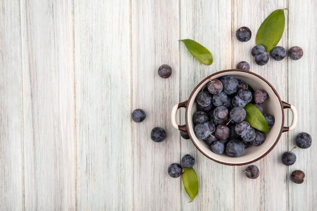 Vue de dessus de la petite prunelle bleu-noir aigre sur un bol avec prunelles isolé sur un fond en bois gris avec espace copie