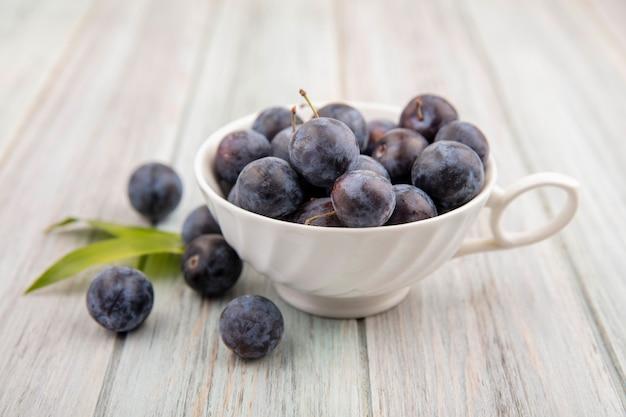 Vue de dessus de la petite prunelle bleu-noir aigre sur une tasse blanche avec des feuilles sur un fond en bois gris