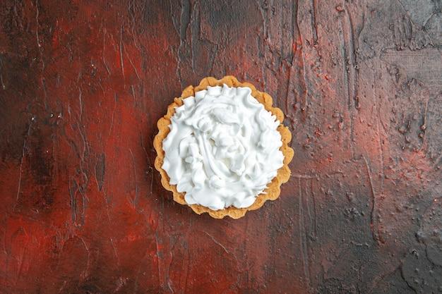 Vue de dessus de la petite tarte à la crème pâtissière sur une surface rouge foncé