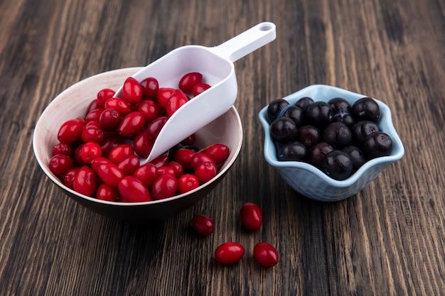 Vue de dessus de petites baies de cornouiller rouge frais sur un bol avec prunellier sur un bol bleu sur un fond en bois