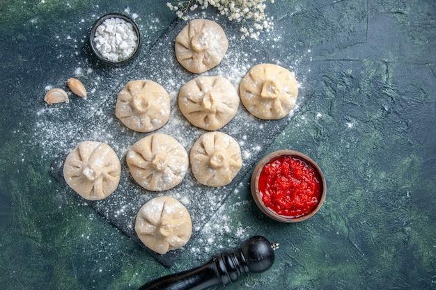 Vue de dessus de petites boulettes crues avec de la viande à l'intérieur sur une surface sombre de la farine de la viande de la viande de couleur poivre de cuisson de la pâte de plat de cuisine