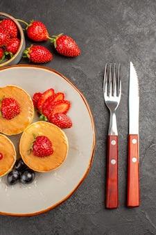 Vue de dessus de petites crêpes délicieuses avec des fruits sur le gâteau de tarte au sol gris foncé