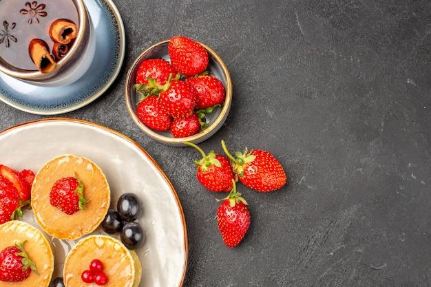 Vue de dessus de petites crêpes délicieuses avec des fruits et une tasse de thé sur la surface grise gâteau aux fruits à tarte