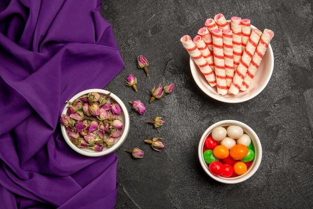 Vue de dessus de petites fleurs violettes avec du tissu violet et des bonbons sur gris