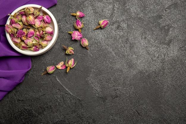 Vue de dessus de petites fleurs violettes avec du tissu violet sur gris
