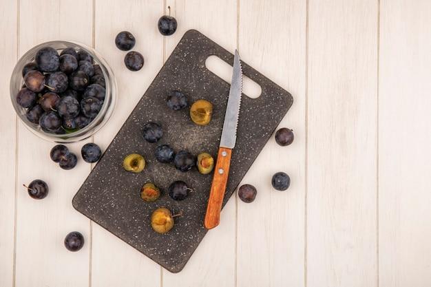 Vue de dessus des petites prunelles de fruits bleu-noir aigre sur un bocal en verre avec des tranches de prunelles sur une planche à découper de cuisine avec un couteau sur un fond en bois blanc