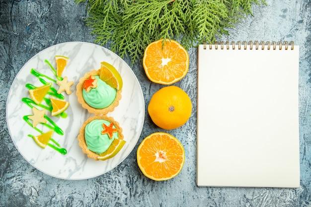 Vue de dessus de petites tartelettes à la crème pâtissière verte et tranche de citron sur le bloc-notes des oranges coupées plaque sur table sombre