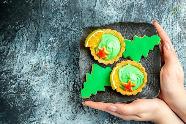 Vue de dessus de petites tartes biscuits arbre de noël sur plaque noire dans la main féminine sur l'espace libre de table gris