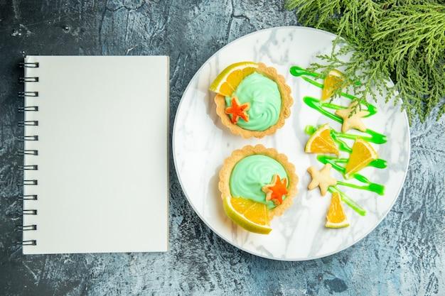 Vue de dessus petites tartes à la crème pâtissière verte et tranche de citron sur le bloc-notes de branche de pin plaque sur table sombre