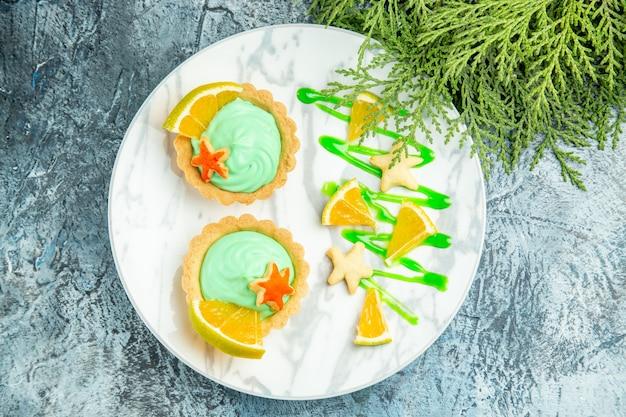 Vue de dessus de petites tartes à la crème pâtissière verte et tranche de citron sur la branche de pin plaque sur table sombre