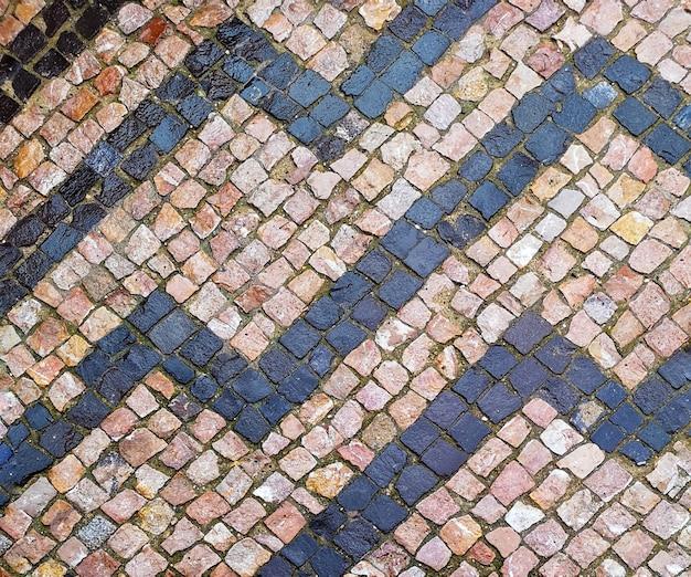 Vue de dessus des petites tuiles de rue après la pluie. trottoir de granit, pavé.
