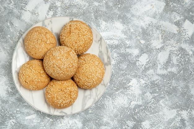 Vue de dessus de petits biscuits moelleux délicieux dessert pour le thé à l'intérieur d'une assiette sur une surface blanche