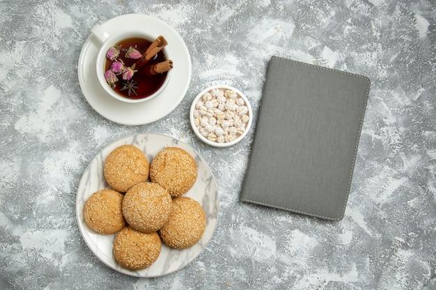 Vue de dessus de petits biscuits moelleux délicieux dessert pour le thé avec une tasse de thé sur une surface blanche