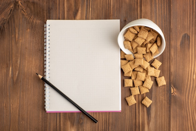 Vue de dessus petits biscuits d'oreiller sur un bureau en bois brun