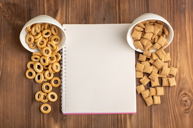 Vue de dessus petits biscuits d'oreiller avec des craquelins sur un bureau en bois brun
