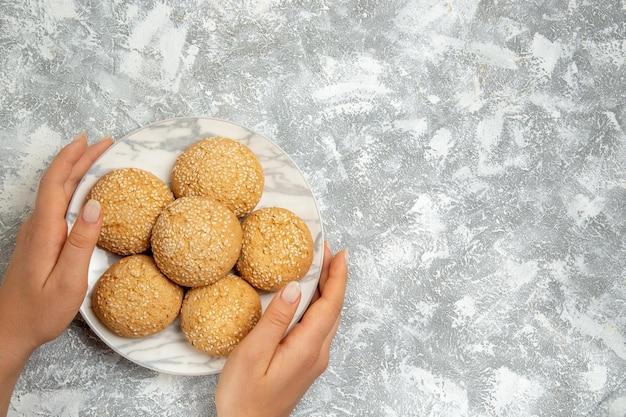 Vue de dessus petits biscuits ronds biscuits moelleux pour le thé sur une surface blanche