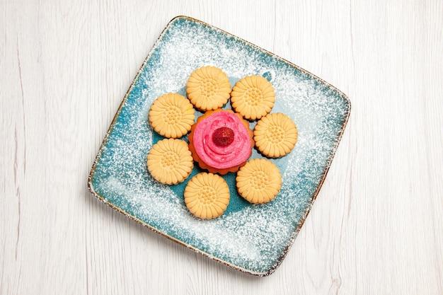Vue de dessus de petits biscuits sucrés avec gâteau aux fruits à l'intérieur de la plaque sur un tableau blanc