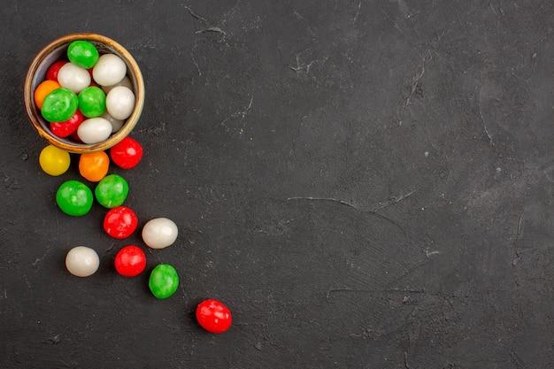 Vue de dessus de petits bonbons colorés sur fond noir