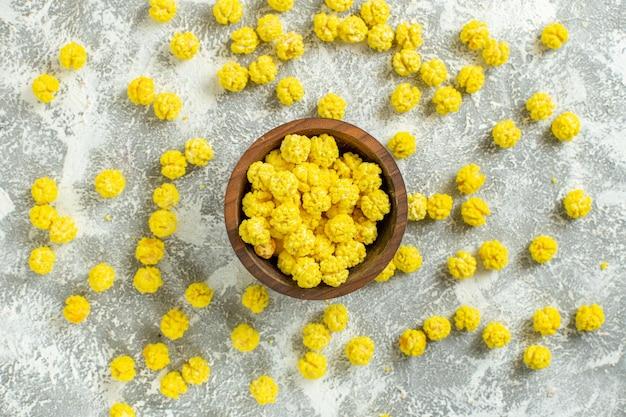 Vue de dessus de petits bonbons jaunes sur une surface blanche, couleur de nombreux bonbons granulés
