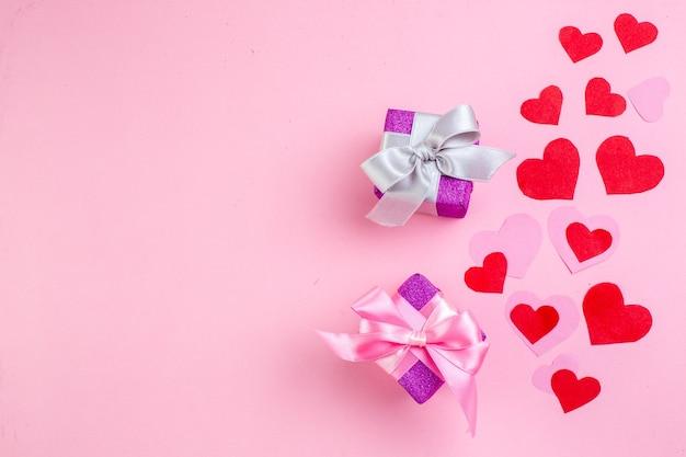 Vue de dessus petits cadeaux autocollants coeur rouge sur fond rose avec lieu de copie