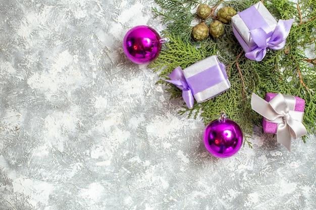 Vue de dessus petits cadeaux branches de pin jouets d'arbre de noël sur une surface grise