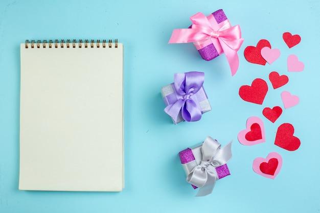 Vue de dessus petits cadeaux cahier coeurs rouges et roses sur fond bleu
