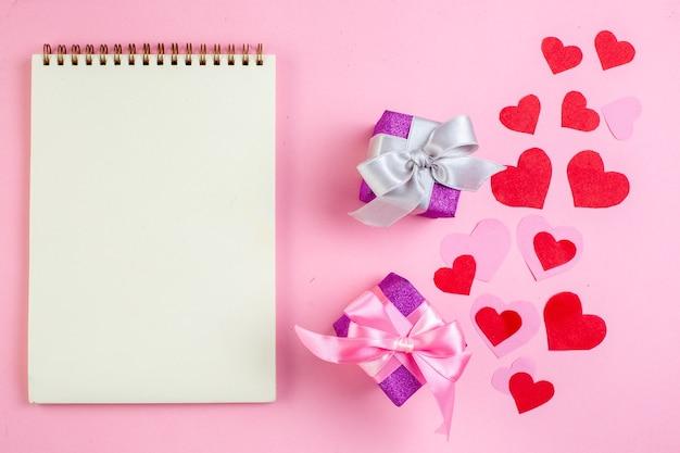 Vue de dessus petits cadeaux coeur rouge autocollants cahier sur fond rose