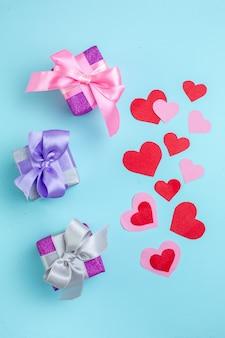 Vue de dessus petits cadeaux coeurs rouges et roses sur fond bleu