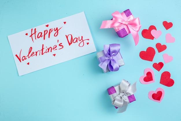 Vue de dessus petits cadeaux coeurs rouges et roses joyeux saint valentin écrit sur papier sur fond bleu