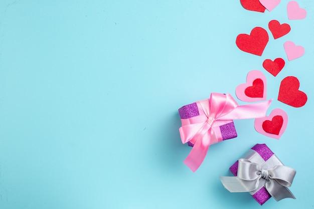 Vue de dessus de petits cadeaux colorés coeurs rouges et roses sur fond bleu avec lieu de copie