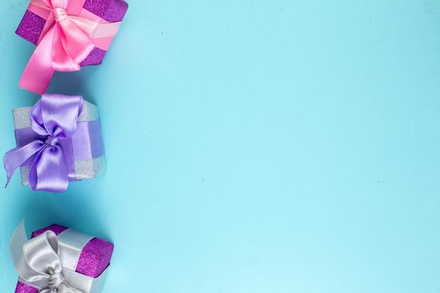 Vue de dessus de petits cadeaux colorés sur fond bleu avec lieu de copie