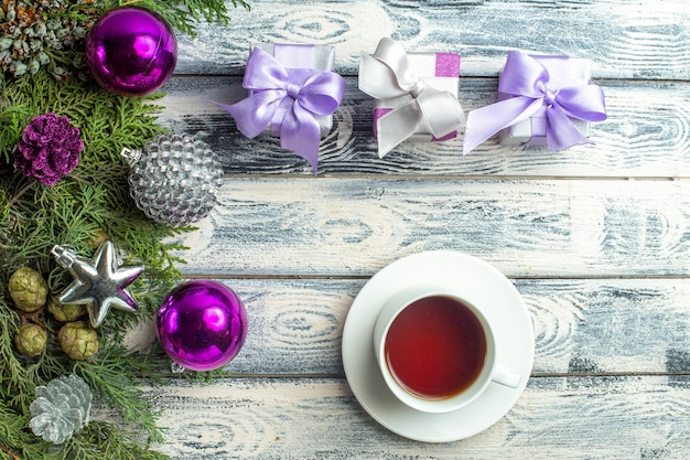 Vue de dessus petits cadeaux jouets d'arbre de noël branches de sapin une tasse de thé sur une surface en bois