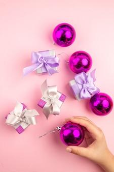 Vue de dessus de petits cadeaux avec des jouets d'arbre de noël sur une surface rose